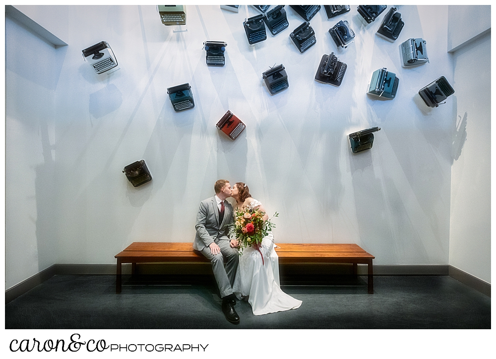a bride and groom kiss underneath a wall of vintage typewriters at the Press Hotel Portland Maine