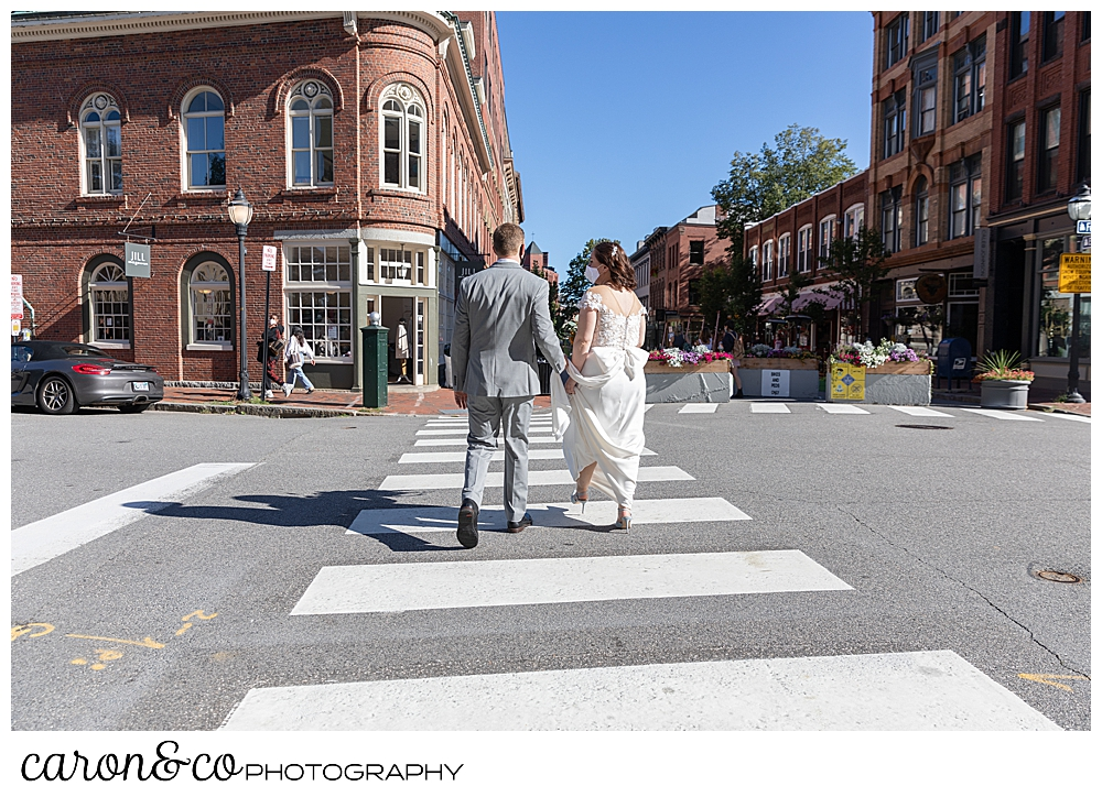 a bride and groom walk across a street in Portland Maine