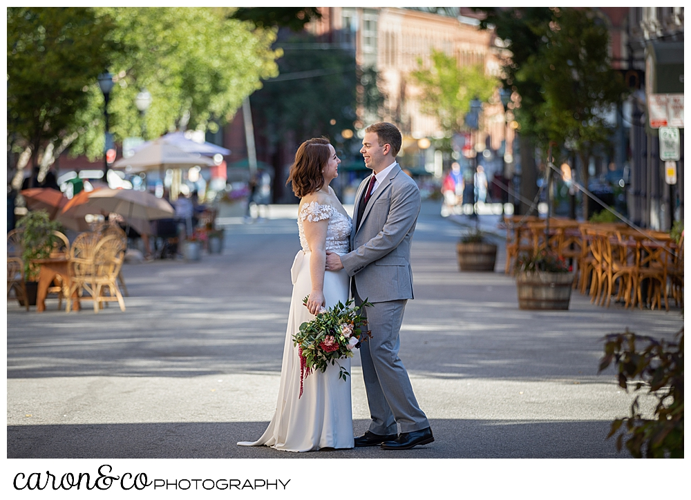 a bride and groom standing in the middle of the road in Portland Maine