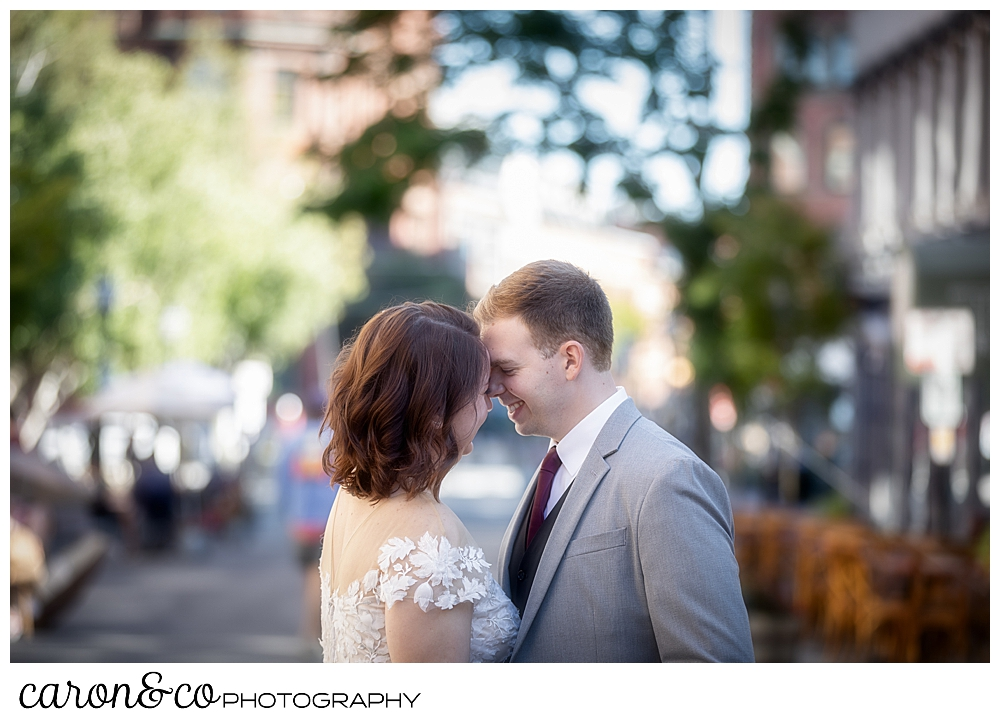 a bride and groom are touching their foreheads together and laughing