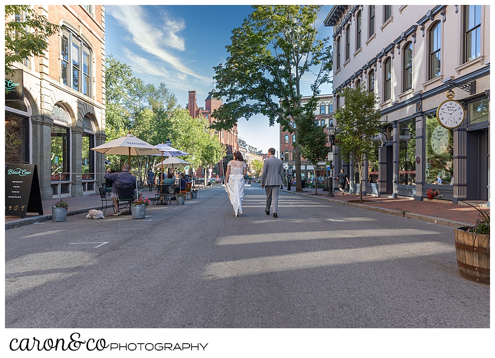 bride and groom walking down the middle of the road in Portland Maine