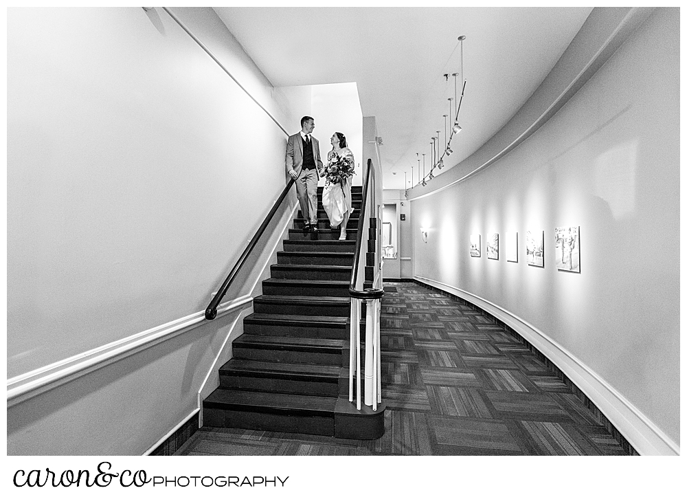 black and white photo of a bride and groom walking down the stairs in an apartment building