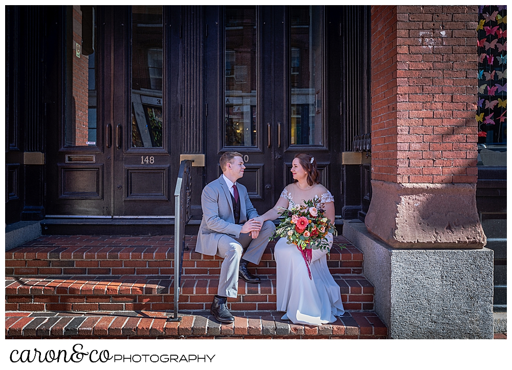 bride and groom sitting on the front steps of an apartment building
