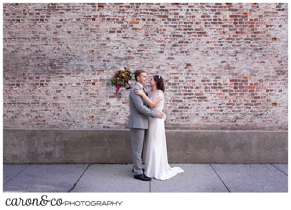 a bride and groom slow dance in front of a brick wall in Portland Maine