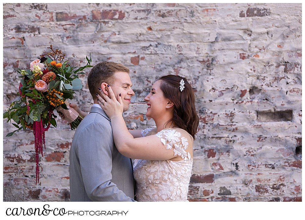 a bride and groom are standing face to face, the bride's hand is on the groom's face