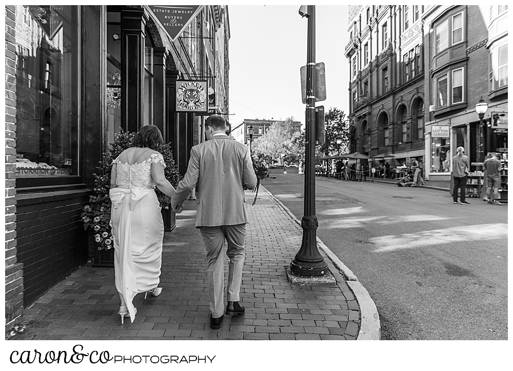 black and white photo of a black and white photo of a bride and groom walking down a sidewalk in Portland Maine