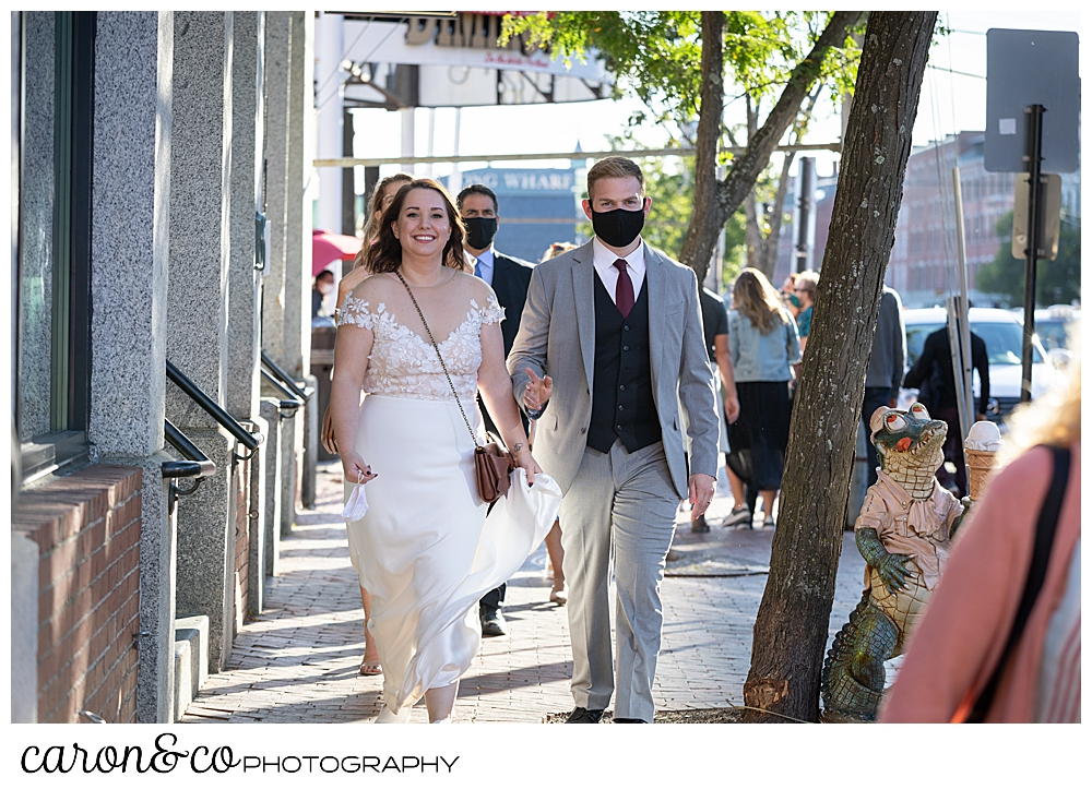 a bride and groom walk down the sidewalk in Portland Maine