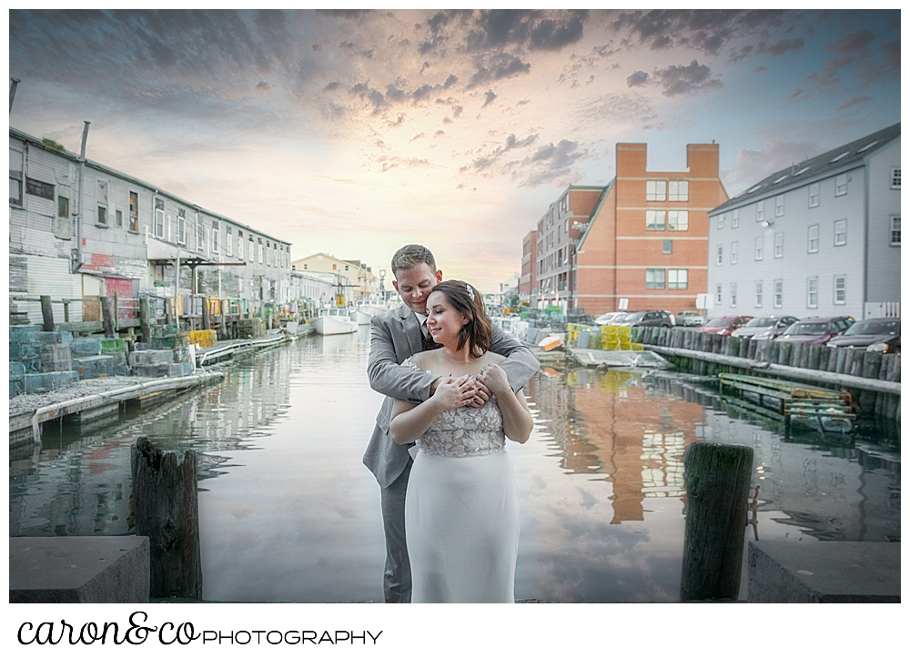 a groom hugs a bride from behind, in front of Portland Maine Harbor