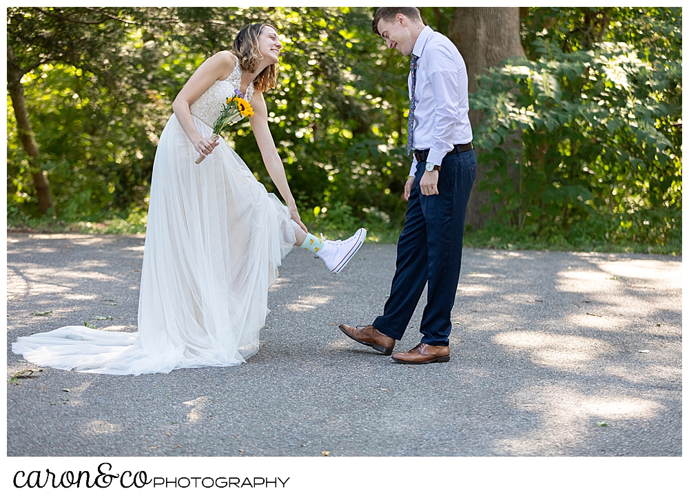 bride living up her foot to show her groom her socks and Converse sneakers