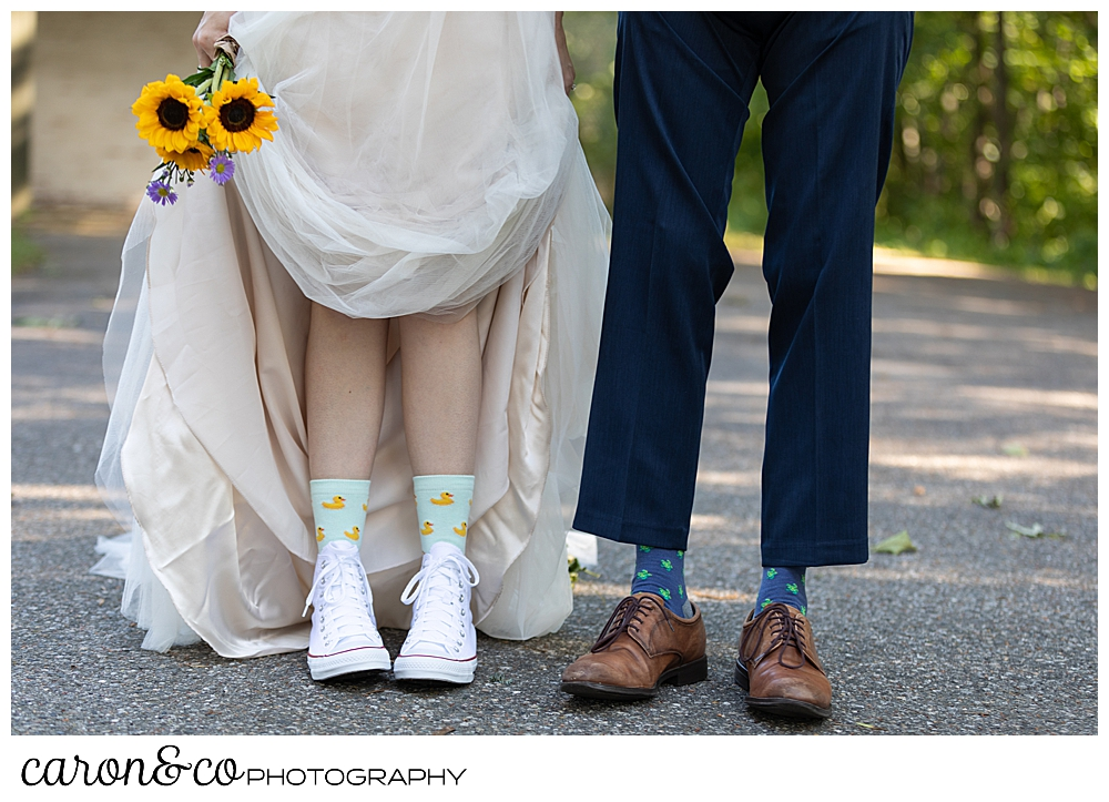 bride and groom standing side by side, bride is holding her dress, you can see their fun socks and shoes