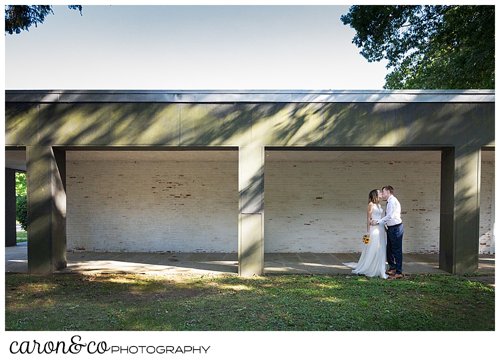 bride and groom kissing each other in front of a building in the woods