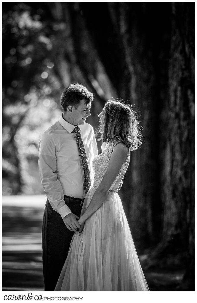 black and white photo of a bride and groom standing close together, looking at one another