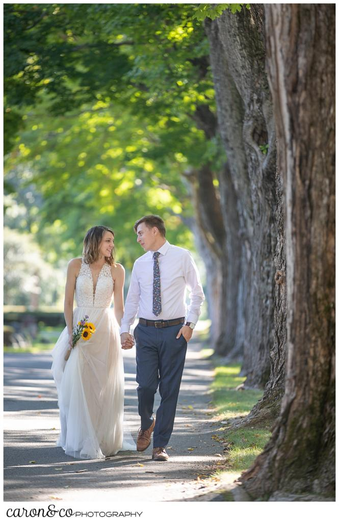 bride and groom walking along a road lined with tall trees