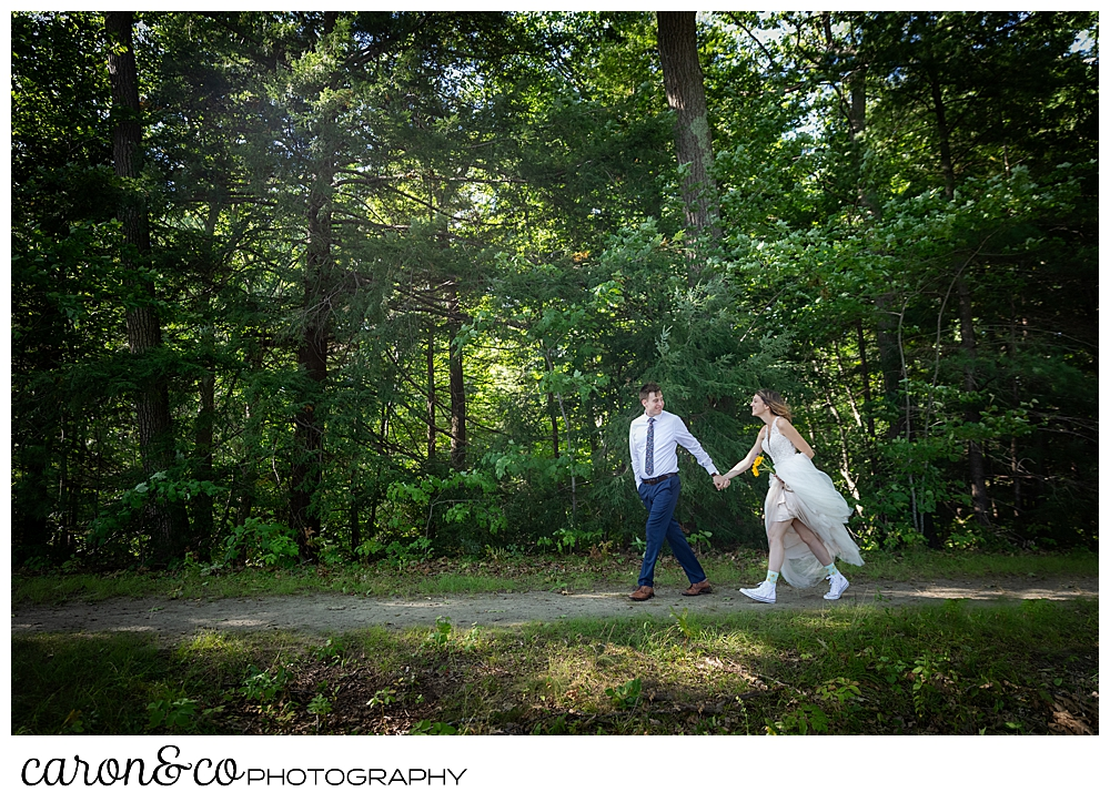 bride and groom walking hand in hand in the woods
