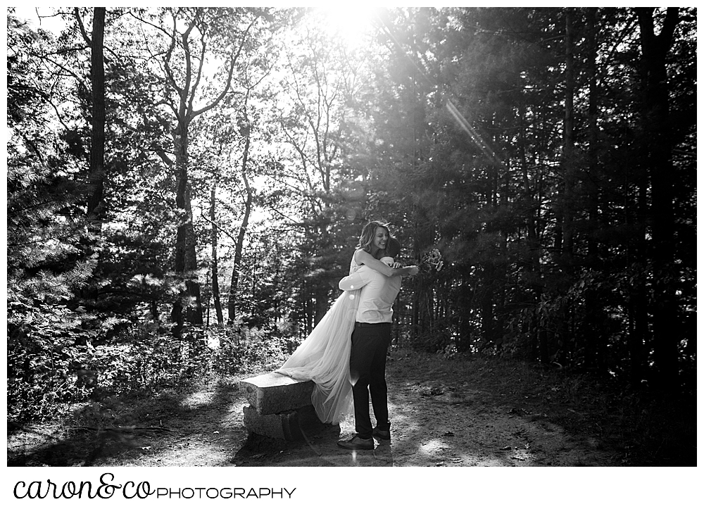 black and white photo of a bride on a bench, jumping into her groom's arms