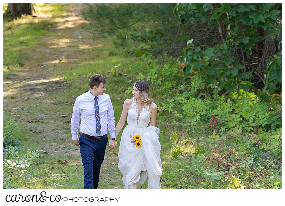 bride and groom walking in the woods, hand in hand