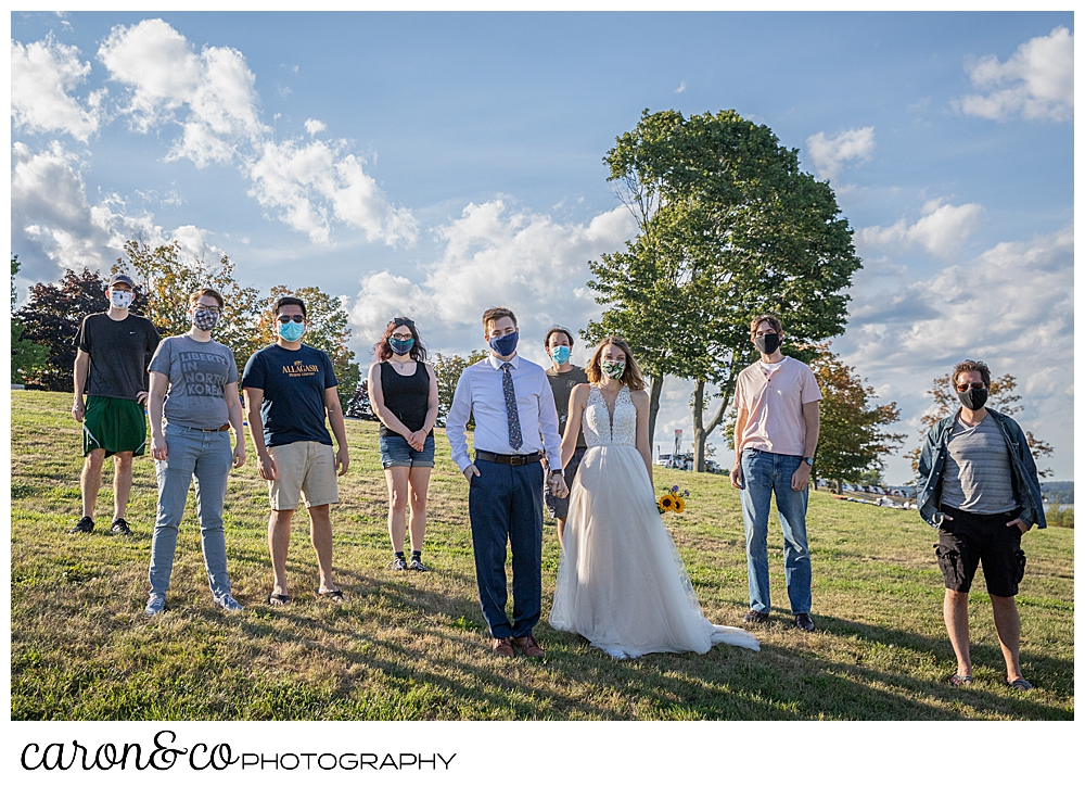Bride and groom standing on a hill with their friends, they're all wearing masks for cover-19