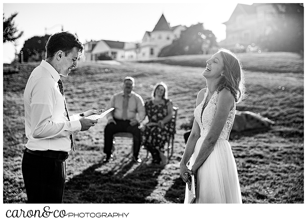 black and white photo of a bride and groom standing together, the groom is reading his vows, the bride's head is back and she is laughing during their sweet Portland Maine elopement