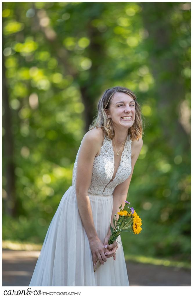 bride leaning forward and smiling during her wedding day first look