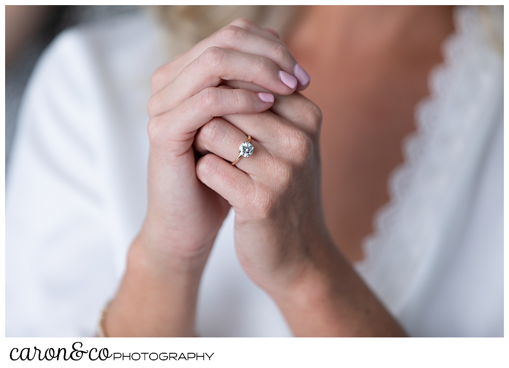 a woman's hands are clasped, you can see her diamond engagement ring