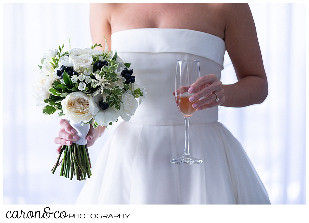 a bride stands holding a beautiful bouquet in one hand, and a glass of champagne in the other, you can't see her head