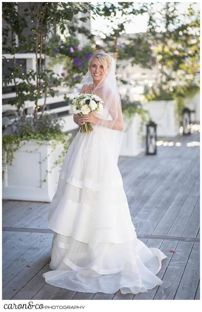 a full length portrait of abeautiful bride, wearing a strapless Carolina Herrara bridal gown and veil, and holding her bouquet
