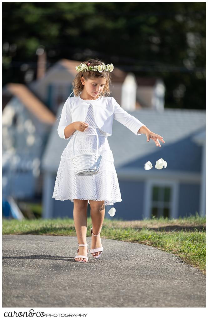 a lower girl, wearing a white dress and floral crown, drops flower petals during a timeless Boothbay Harbor wedding in Maine