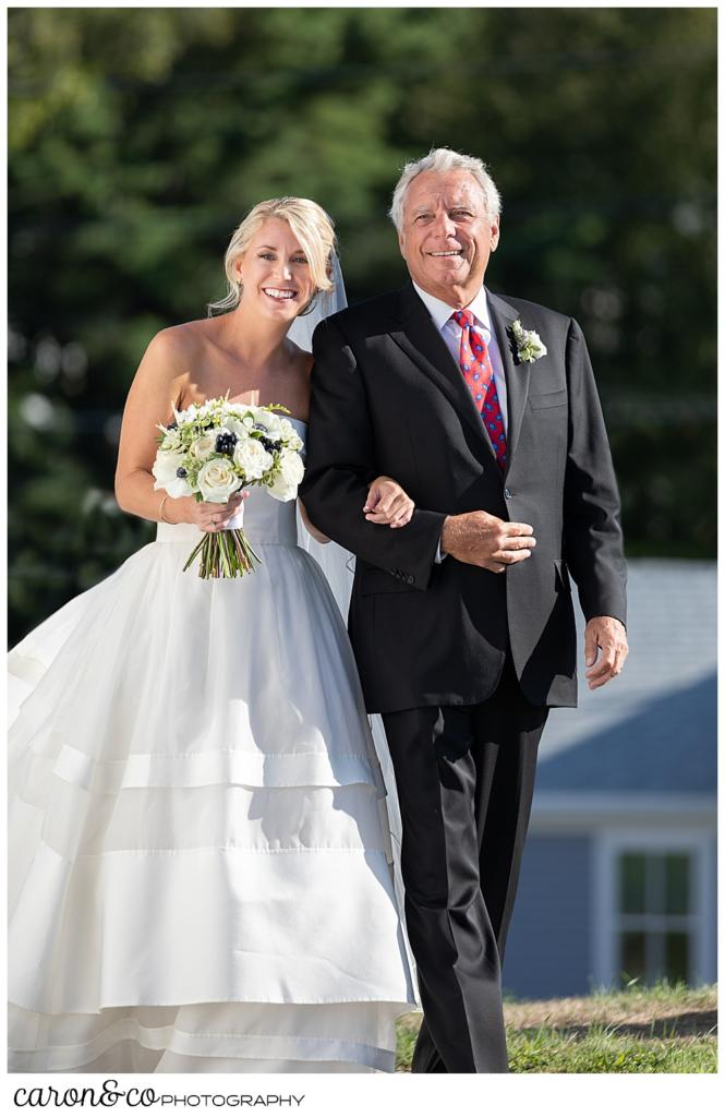 A smiling bride and her father during the processional at a timeless Boothbay Harbor wedding in Maine