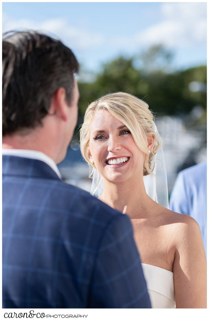 A bride smiles at her groom during a Boothbay Harbor Maine wedding ceremony