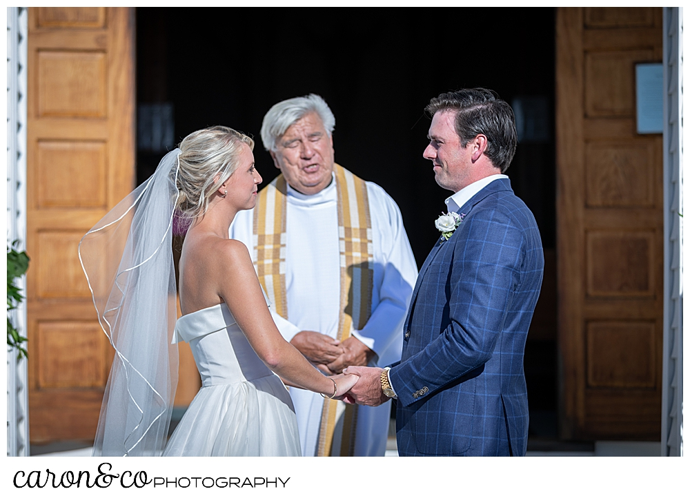 A bride and groom stand before a Catholic priest during their timeless Boothbay Harbor wedding in Maine