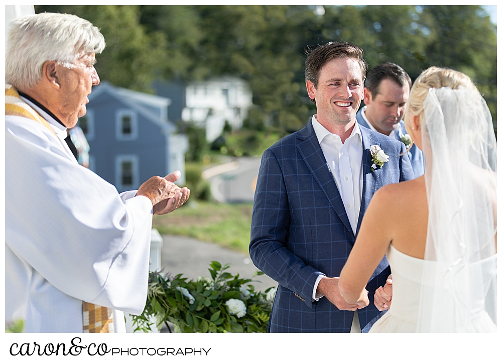 A groom smiles at his bride during their Our Lady Queen of Peace Catholic Church, Boothbay Harbor, Maine