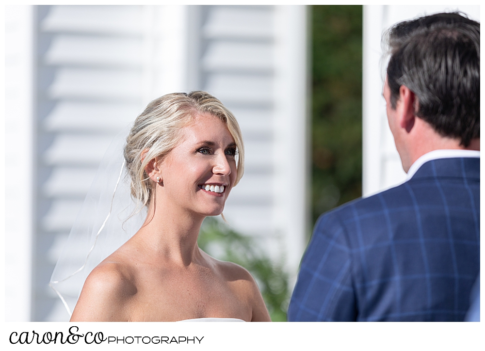 A bride smiles at her groom during their timeless Boothbay Harbor wedding, in Maine