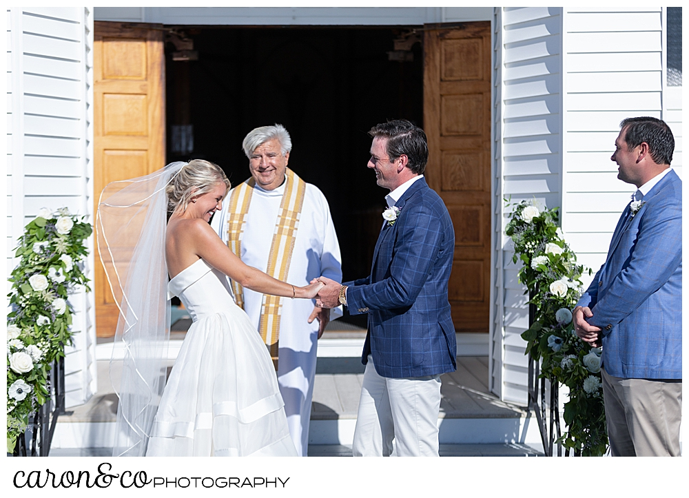 bride and groom smile at each other at their Our Lady Queen of Peace Catholic Church wedding ceremony