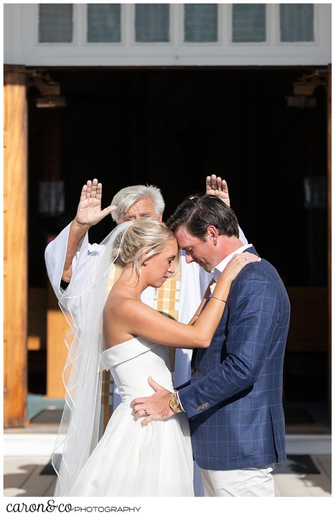 a bride and groom stand with foreheads together, as a priest blesses them at an Our Lady Queen of Peace, timeless Boothbay Harbor wedding