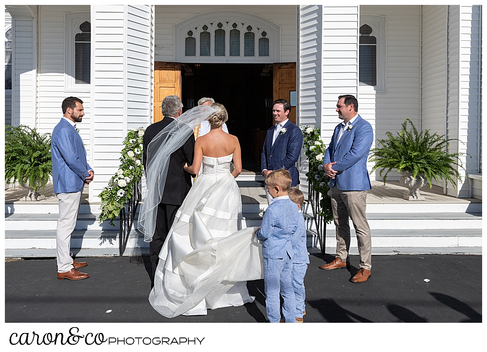 A bride, with two pages carrying her train, and her father approach the front of Our Lady Queen of Peace Catholic Church during a timeless Boothbay Harbor wedding ceremony