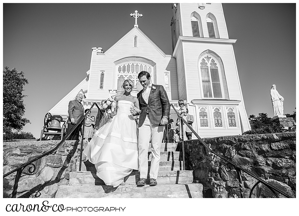 A black and white photo of a bride and groom walking down the steps at Our Lady Queen of Peace, timeless Boothbay harbor wedding