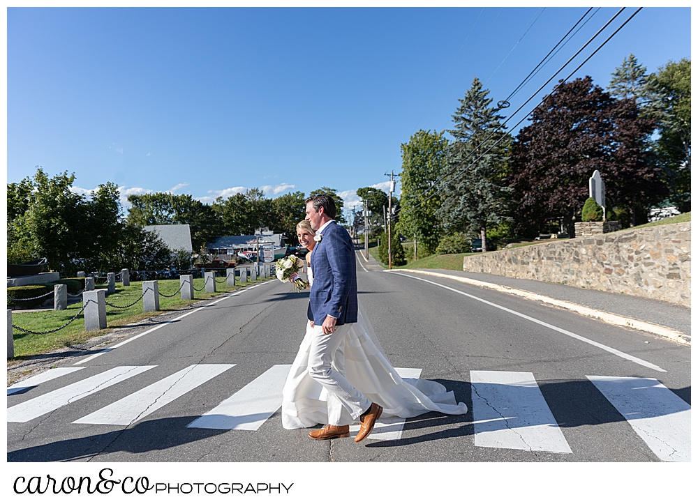 A bride and groom cross the street during their timeless Boothbay Harbor wedding, Boothbay Harbor, Maine