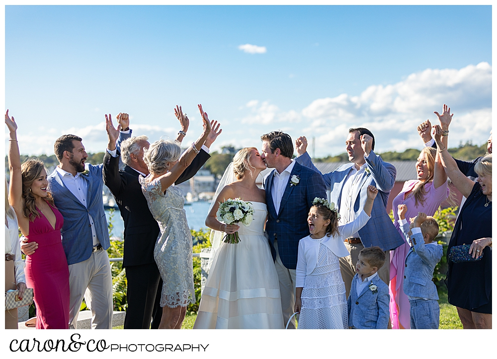 a bride and groom kiss, while their families cheer at their Boothbay Harbor, Maine wedding