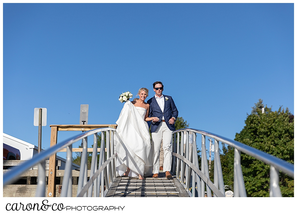 A bride and groom walk down a dock during their Boothbay Harbor, Maine wedding