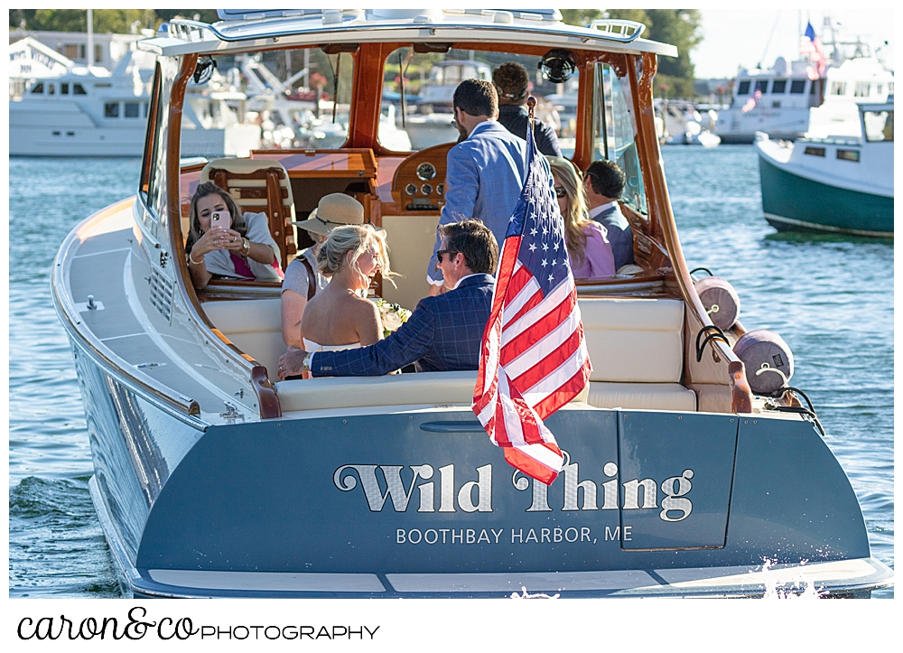 A bride and groom and their bridal party aboard the Hinckley Yachts Picnic Boat Wild Thing, during their timeless Boothbay Harbor wedding, Boothbay harbor, Maine