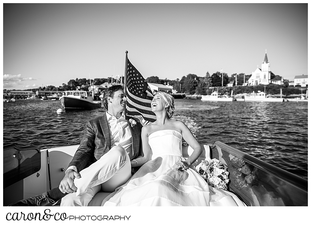 Black and White phot of a bride and groom laughing together as they ride on a Hinckley Yachts Picnic Boat, during their timeless Boothbay harbor wedding, Boothbay Harbor, Maine