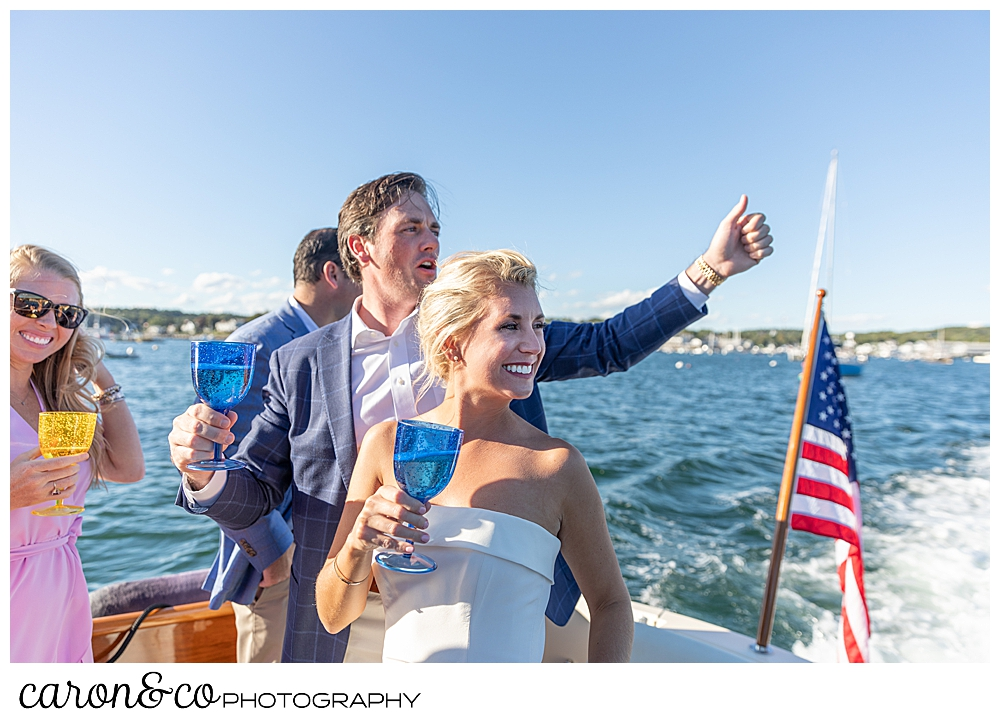 A bride and groom on the back of a Hinckley Yachts Picnic boat, they're holding champagne and waving, during their Boothbay Harbor, Maine wedding