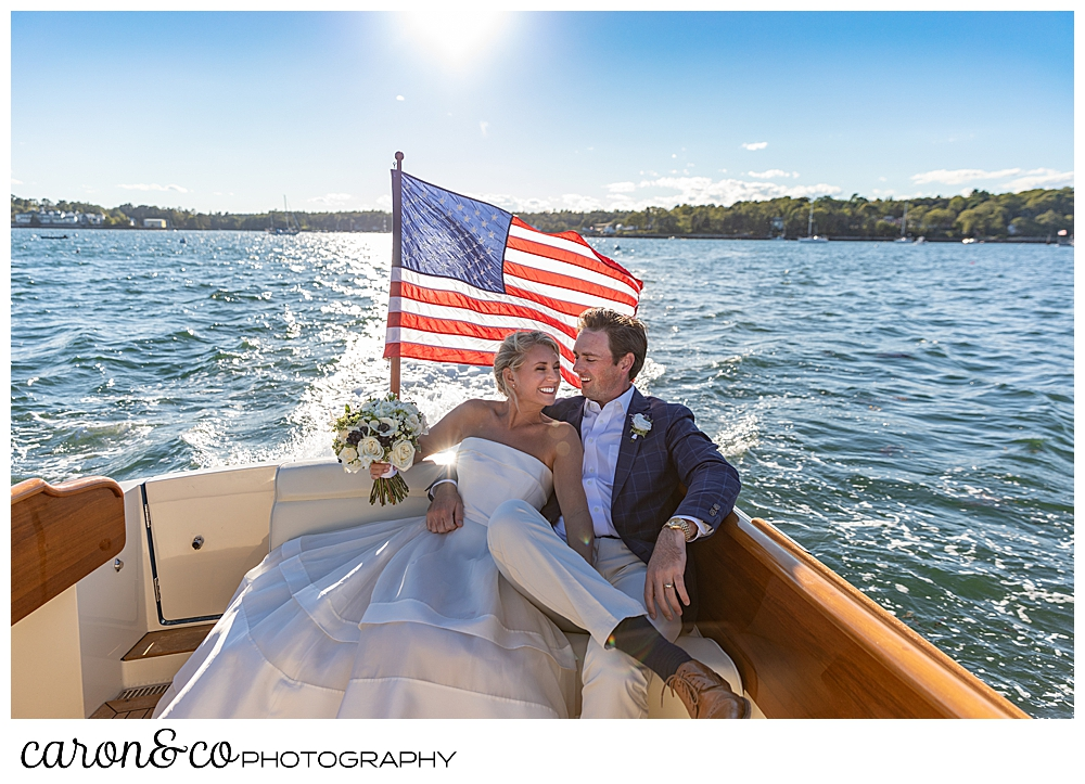A bride and groom sit on a settee on the back of a Hinckley Yachts Picnic boat at their timeless Boothbay Harbor wedding, Boothbay Harbor, Maine