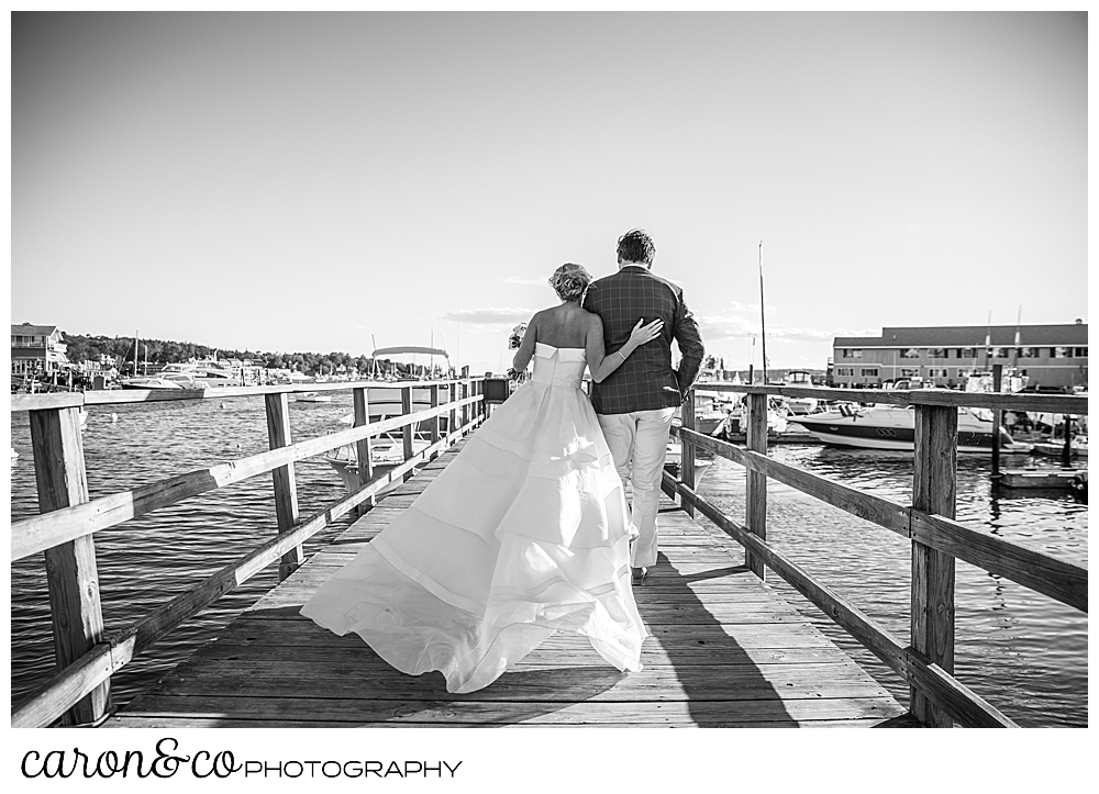 Black and white photo of a bride and groom walking on a dock, their backs are to the camera, the bride's dress is billowing out