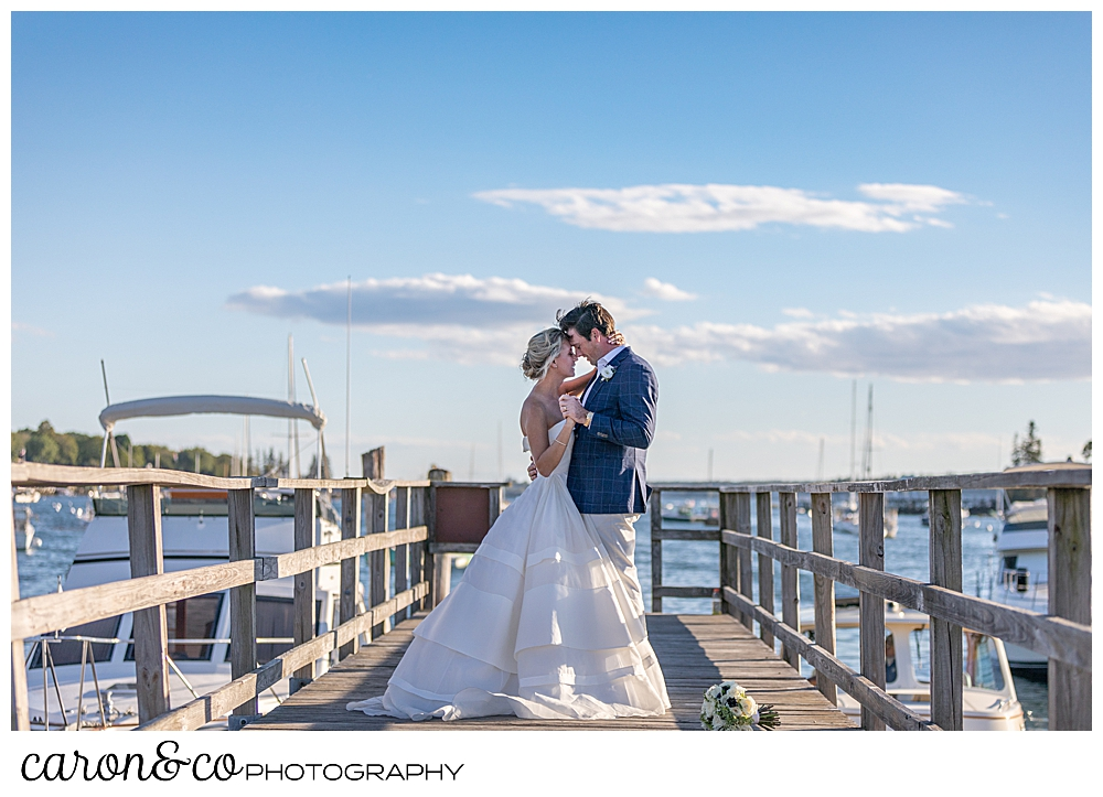 a bride and groom are dancing on a dock, their foreheads are touching, during their timeless Boothbay Harbor wedding