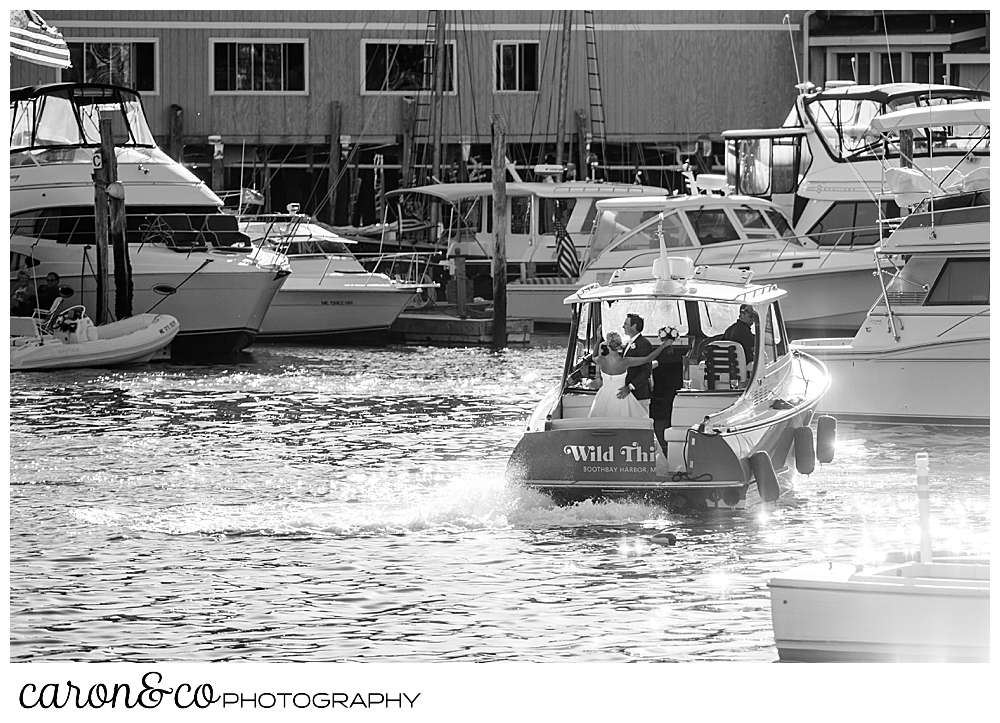 black and white photo of a bride and groom on the back of a Hinckley Yachts Picnic boat in Boothbay Harbor, timeless Boothbay Harbor wedding