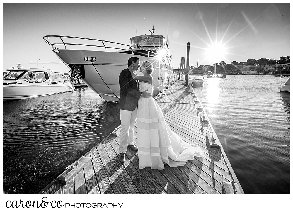 black and white photo of a bride and groom standing together on a dock, next to a motor yacht, during their timeless Boothbay Harbor wedding, Boothbay Harbor, Maine