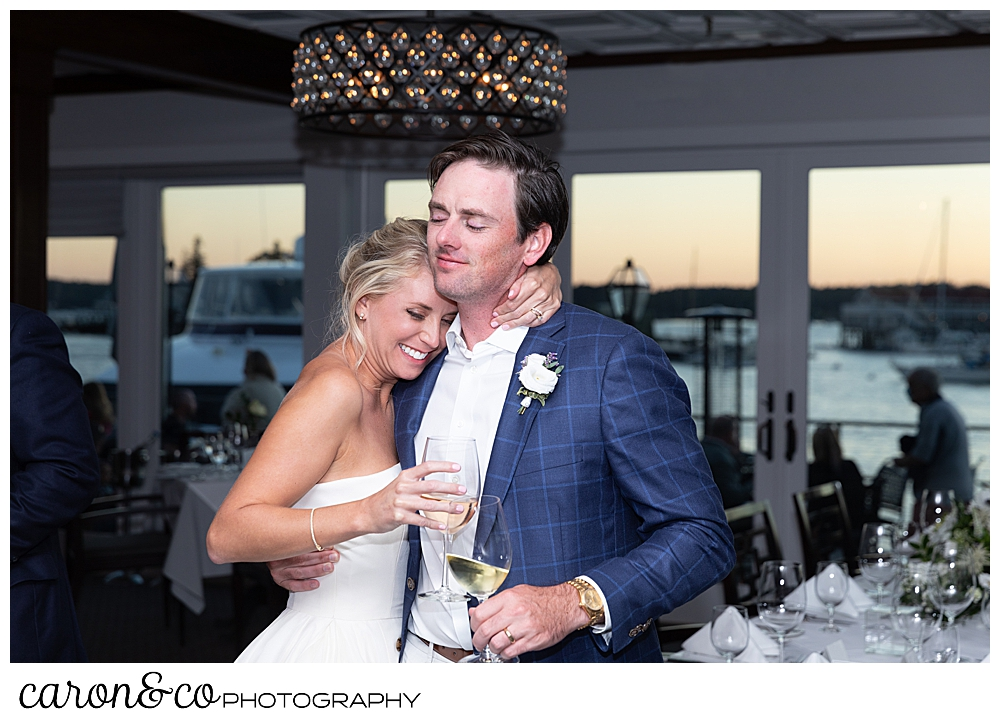 a bride and groom hugging, eyes closed, holding wine glasses during their timeless Boothbay Harbor wedding, Maine