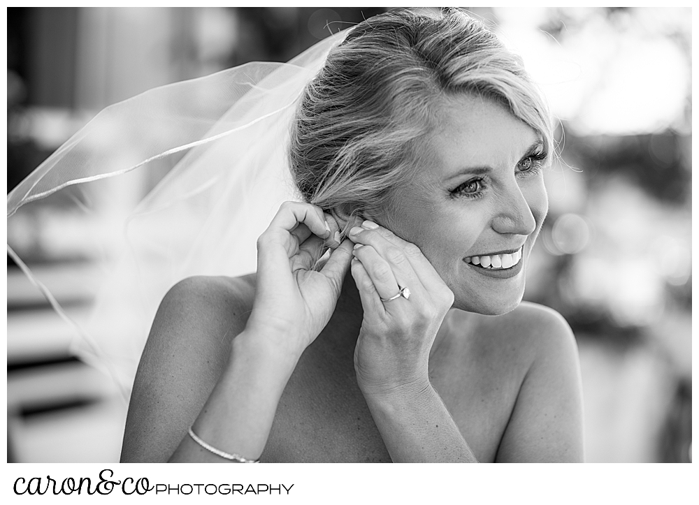 a bride wearing veil, and smiling, is putting on an earring