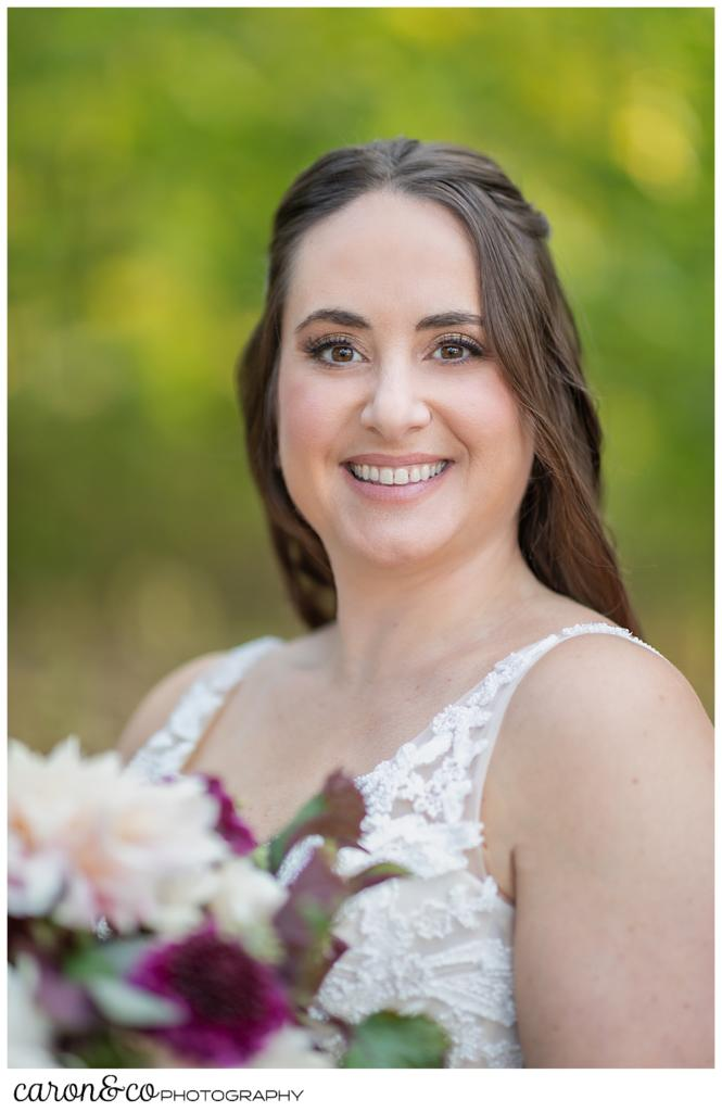 bridal portrait of a dark-haired bride, holding a bouquet of blush and dark red dahlias